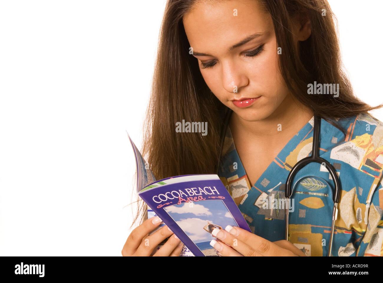 Female Nurse (20-25) Looking at Florida Travel Brochure - Stock Image