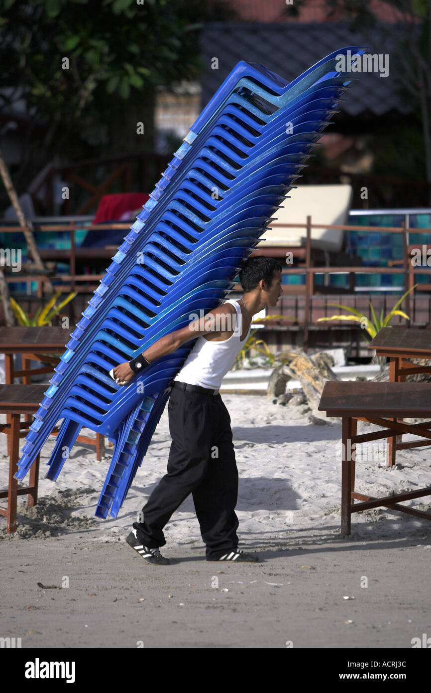 Man Carries Pile Of Plastic Chairs While Setting Up Beach Dining Tables Ko  Chang Thailand