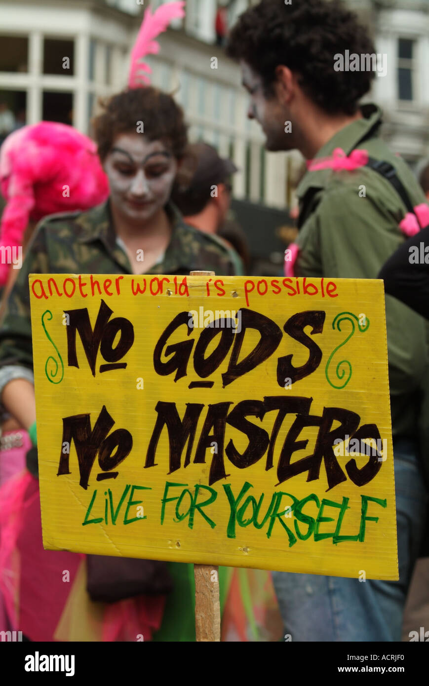 Placard in front of members of the Clandestine Insurgent Rebel Clown Army in the middle of Princes Street - Stock Image