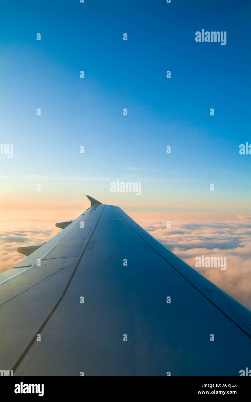 Airplane Wing At Sunset With Clouds - Stock Image