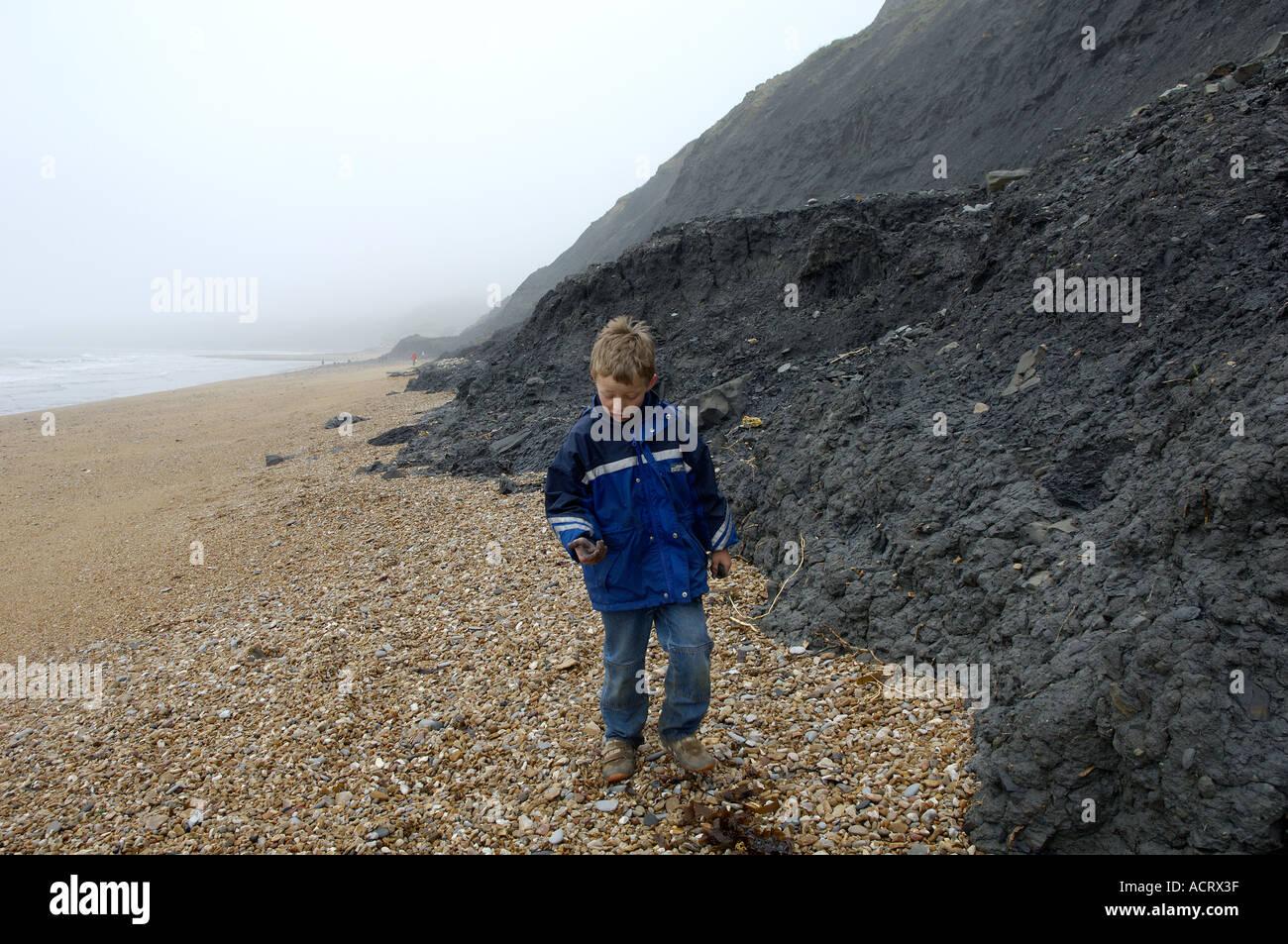 Child at the Jurassic Coast cliffs Charmouth near Lyme Regis Dorset East Devon Coast England Stock Photo
