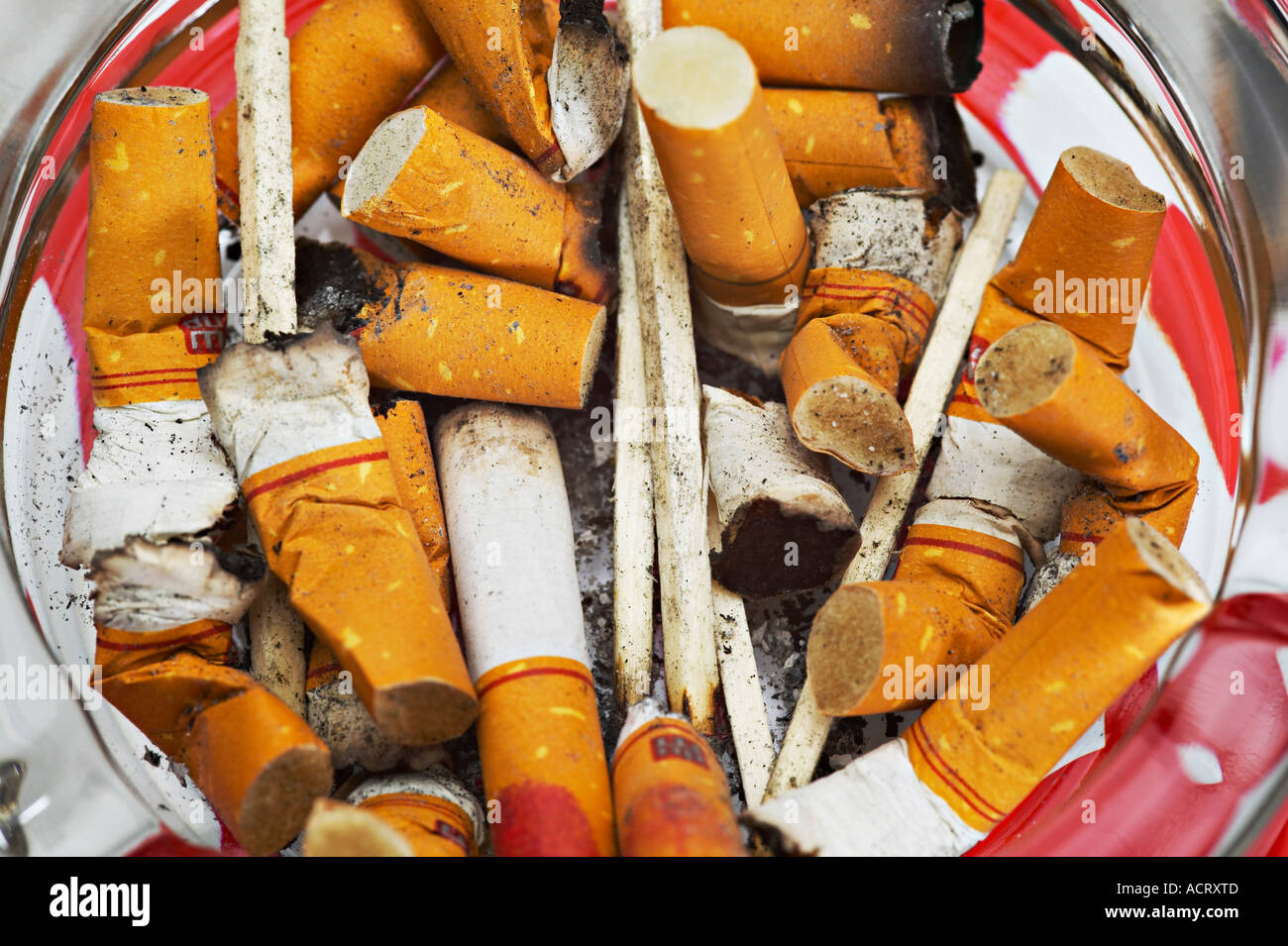 Ashtray filled with cigarette butts and burnt matches - Stock Image