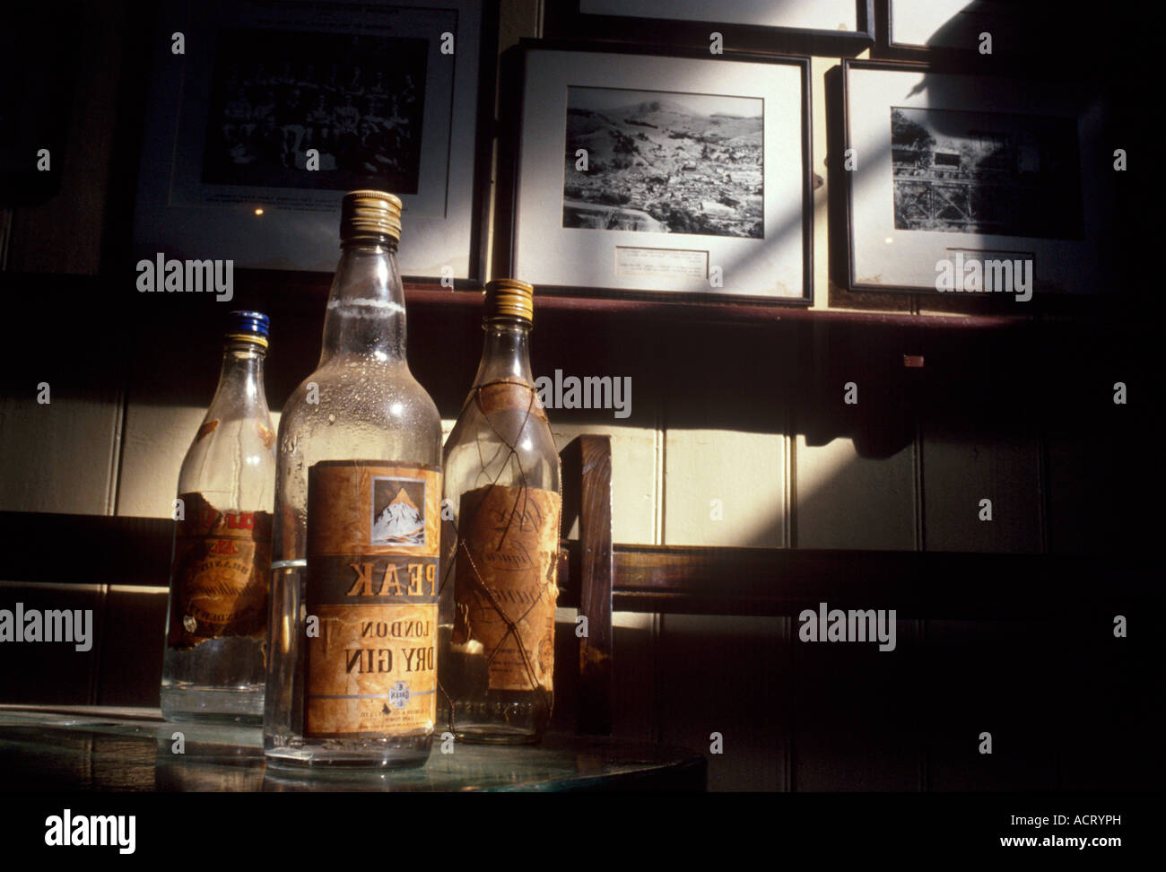 Empty bottles of alcohol stand on a bar with photographs of the gold rush era at the Royal Hotel in Pilgrims rest Stock Photo