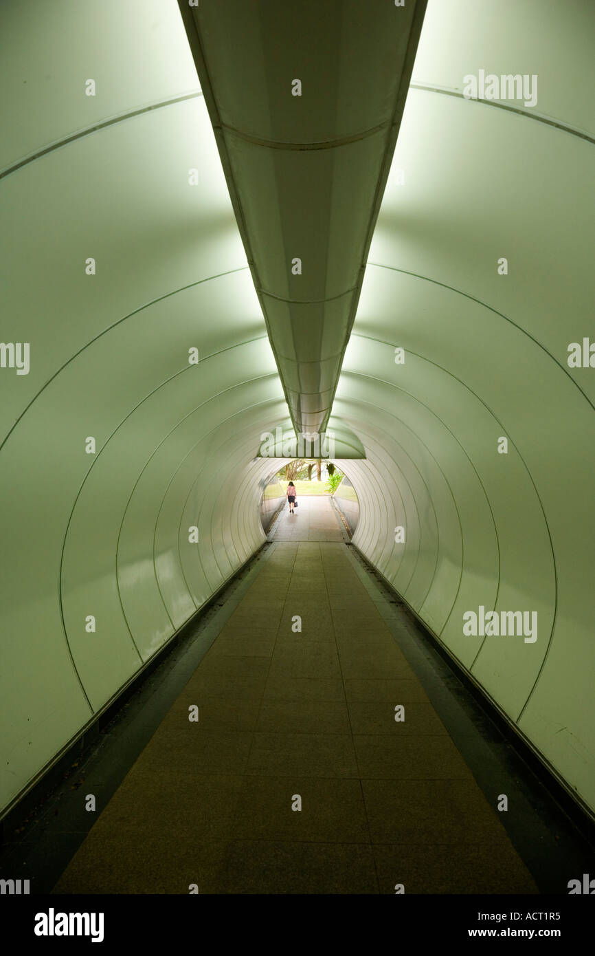 Asian woman walking alone from shiny green metal tunnel There is another shot of the same woman walking into the tunnel - Stock Image