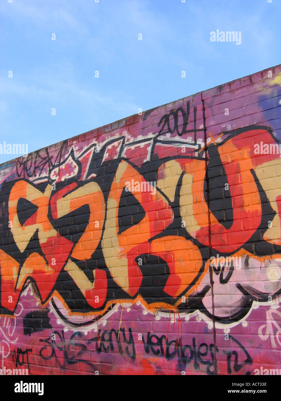 orange and red graffitti on a brick wall with blue sky behind - Stock Image