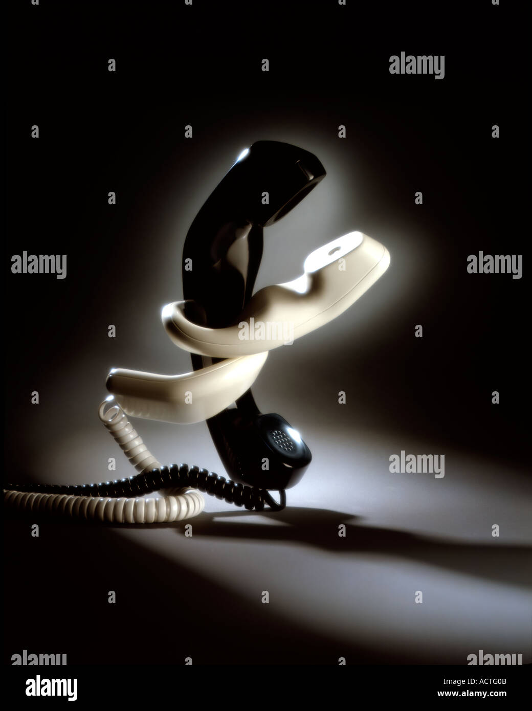 Phones connected two telephones entwined - Stock Image