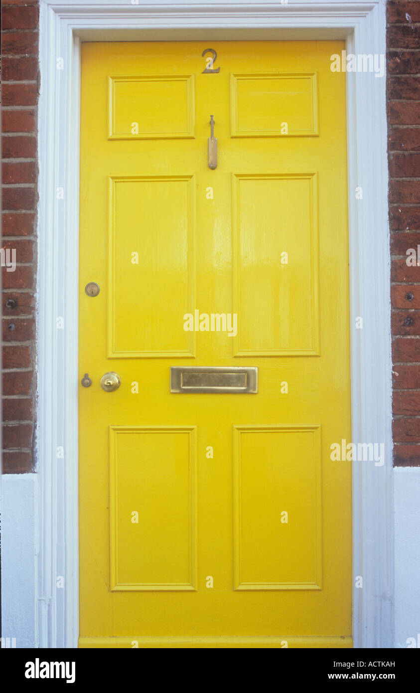 Stylish panelled front door freshly painted yellow with white doorframe and brass cricket-bat knocker letterbox and number & Stylish panelled front door freshly painted yellow with white Stock ...