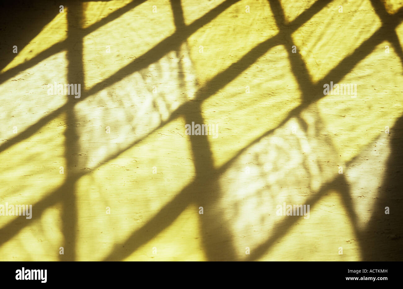 Projection of clear small handmade square or diamond leaded panes of window glass onto cream painted rough wall - Stock Image