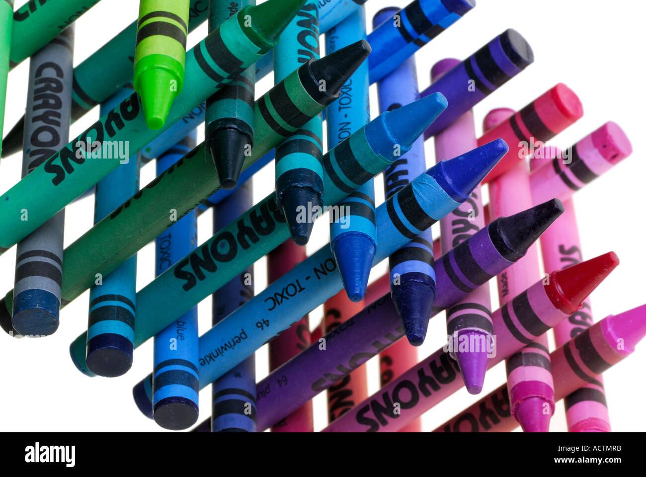 Angled Multi colored crayons stacked up in a cross hatch on white background - Stock Image