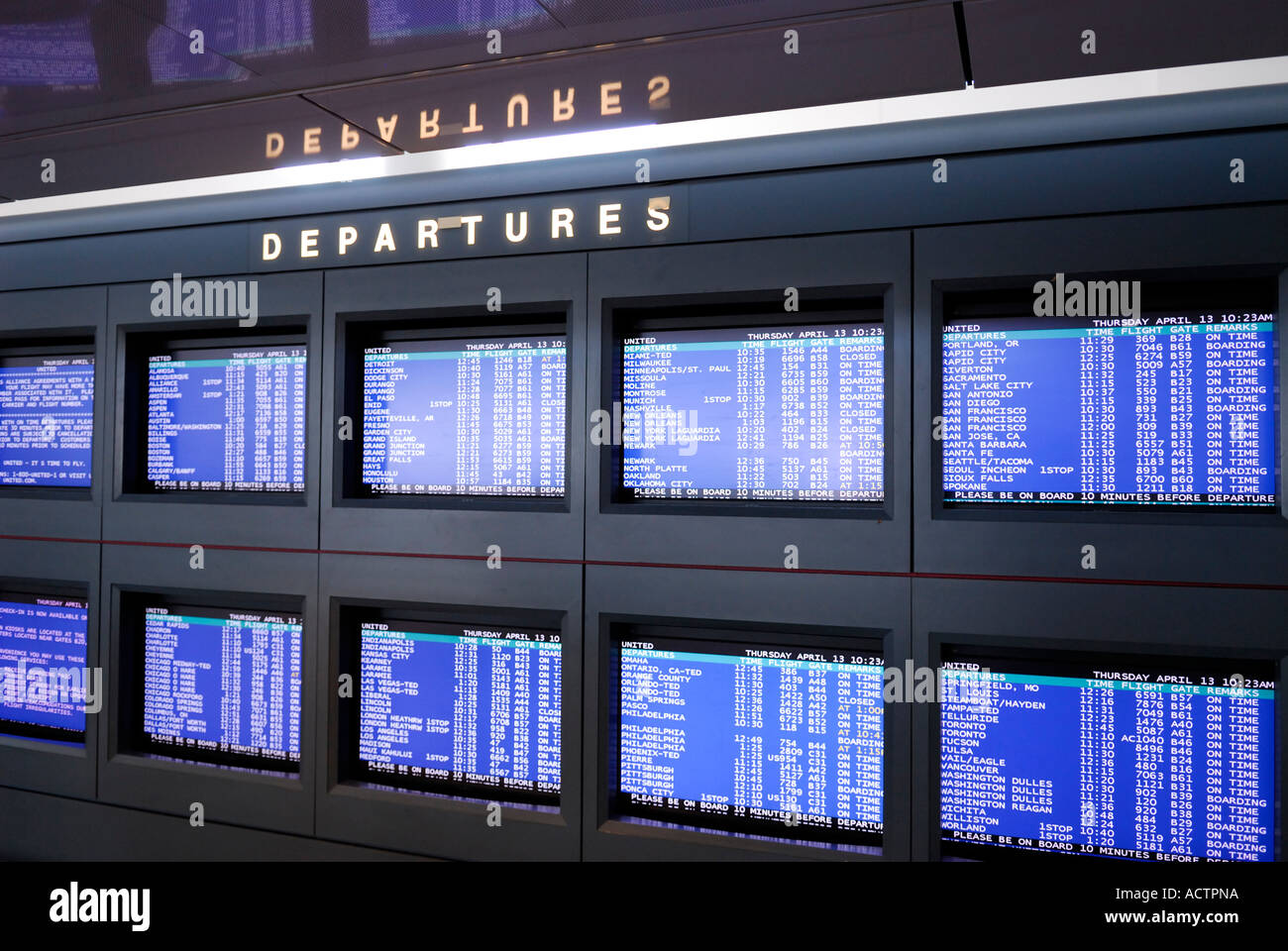 Departure flight TV screens at a large international airport - Stock Image