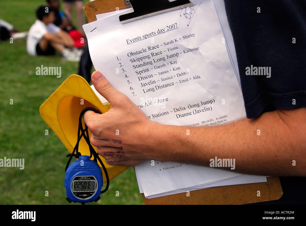 SPORT TEACHER HOLDONG ACTIVITY SHEET AND CHRONOMETER - Stock Image