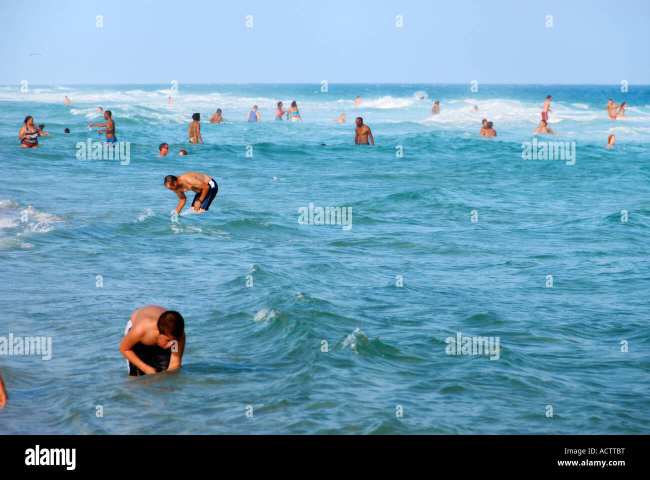 Beach goers wading and searching for seashells Pensacola Beach Florida - Stock Image