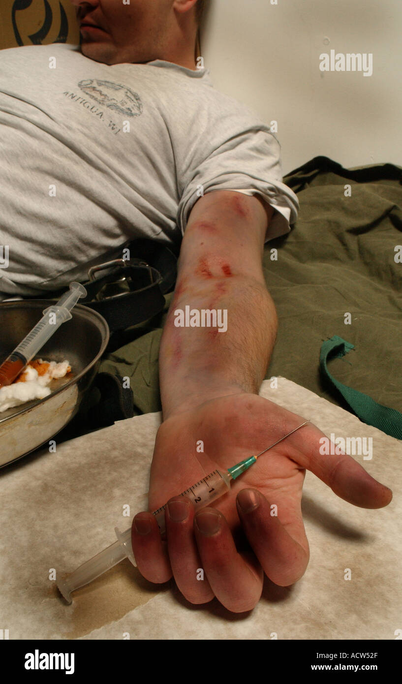 a heroin addict suffering from an overdose after a fix of the drug through a hypodermic needle - Stock Image