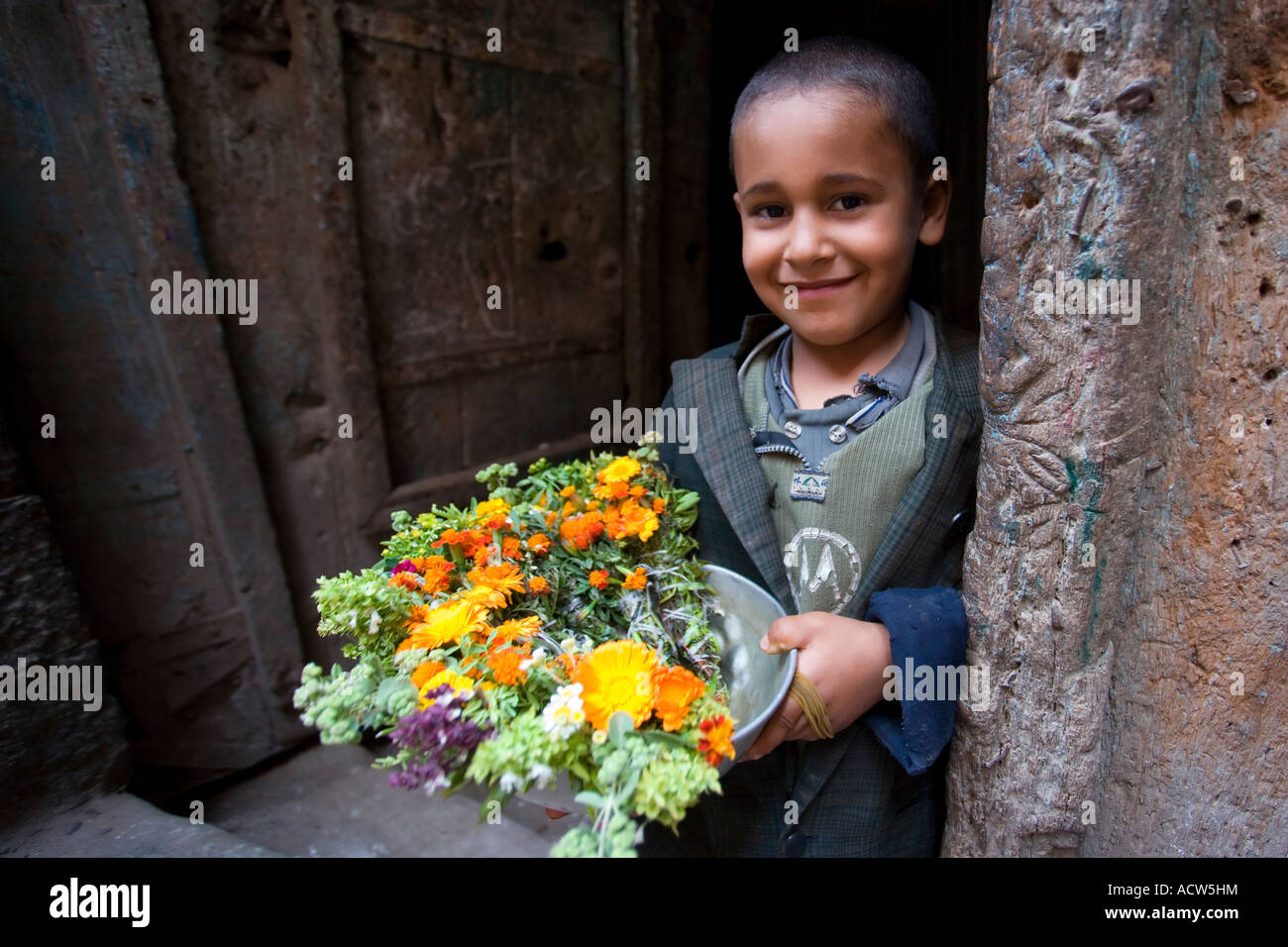 Young boy selling flowers on the streets of the village of Jibla near Taizz Yemen - Stock Image