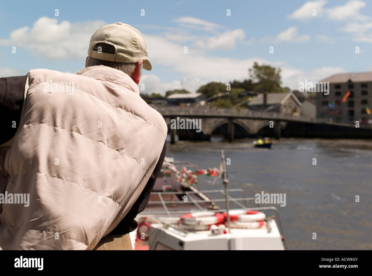rear view of a man looking at boats on the River Teifi (Tivy) Cardigan town (Aberteifi) west  wales Stock Photo