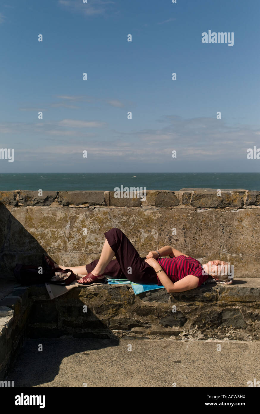 middle-aged woman lying on back on stone harbour wall New Quay Cei Newydd Ceredigion wales summer afternoon sunbathing - Stock Image