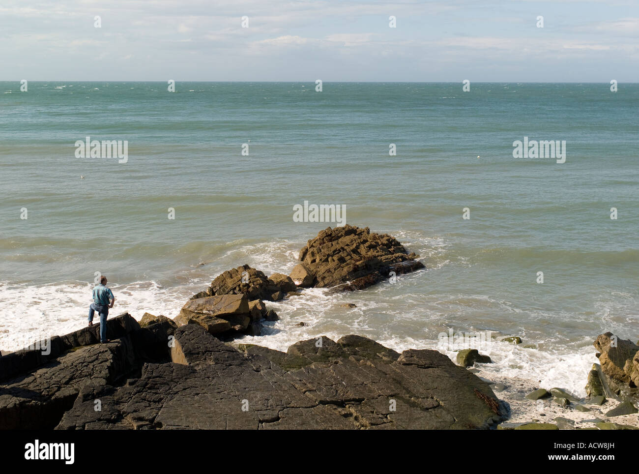 Man standing alone on the rocky shore at New Quay ceredigion looking at the waves on Cardigan Bay west wales UK - Stock Image