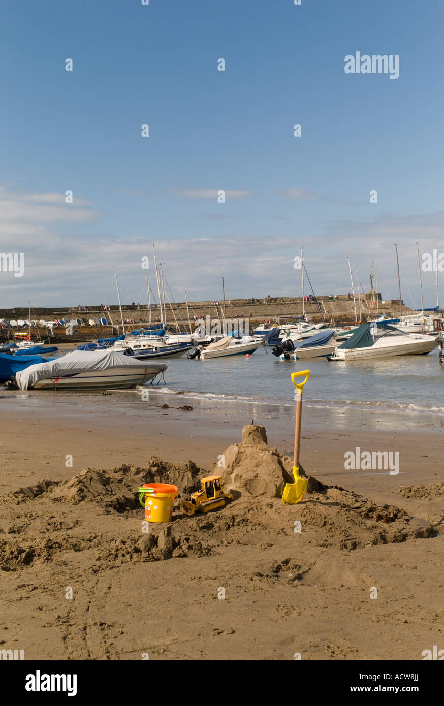 A child's sandcastle bucket and spade on New Quay beach Cardigan Bay west wales with boats moored in the harbour - Stock Image
