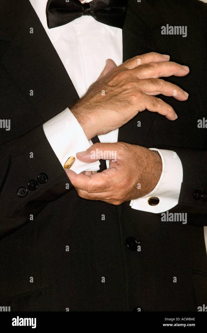 Senior man adjusting cuff links - Stock Image