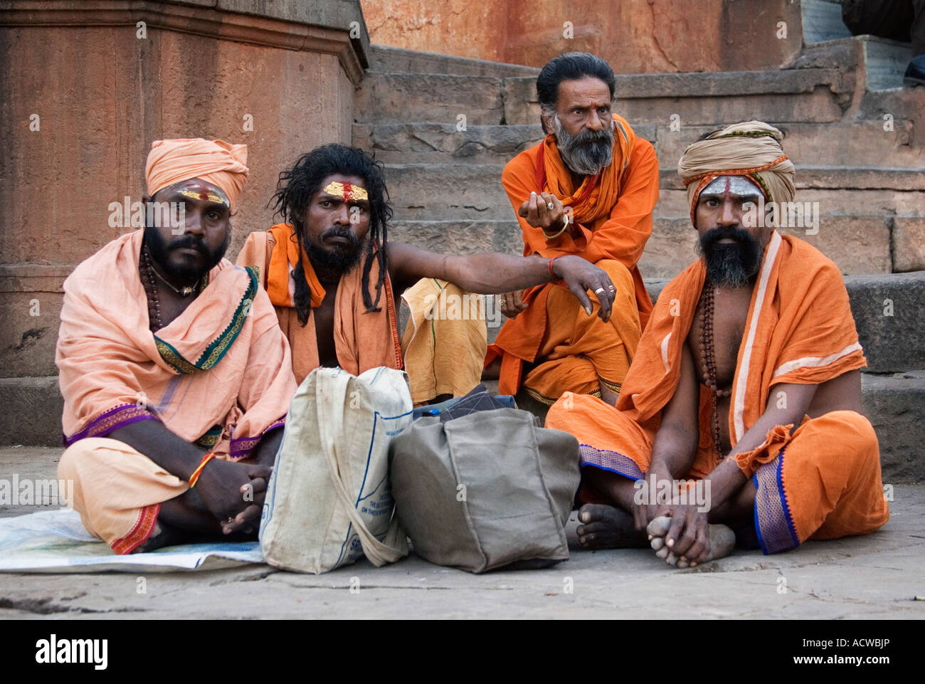 Holy Saddou men at the stairs at the ghats Varanasi Benares India - Stock Image
