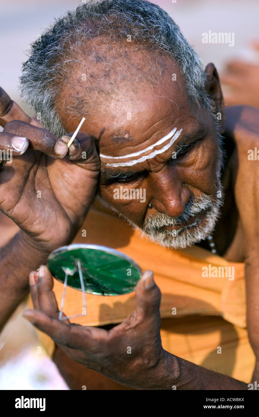 Holy man preparing face paint for prayer Varanasi Benares India - Stock Image