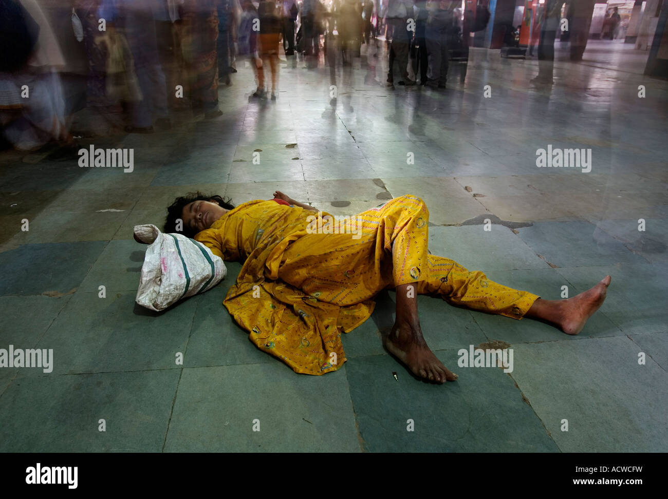 Dalit or untouchable sleeping exhausted in the floor of a train station Delhi India - Stock Image