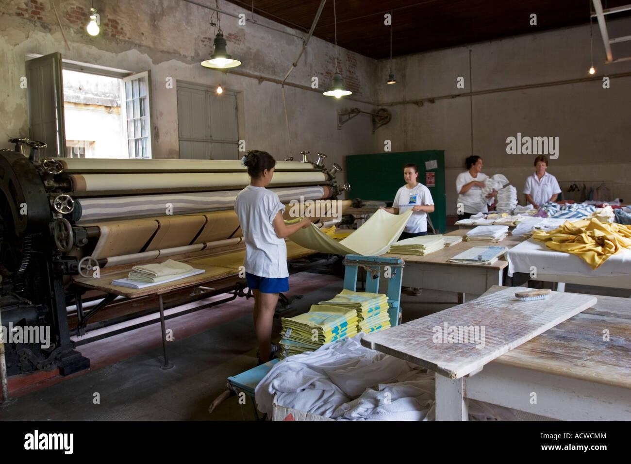 Antique Hotel Laundry Shop Sheet ironing and folding - Stock Image