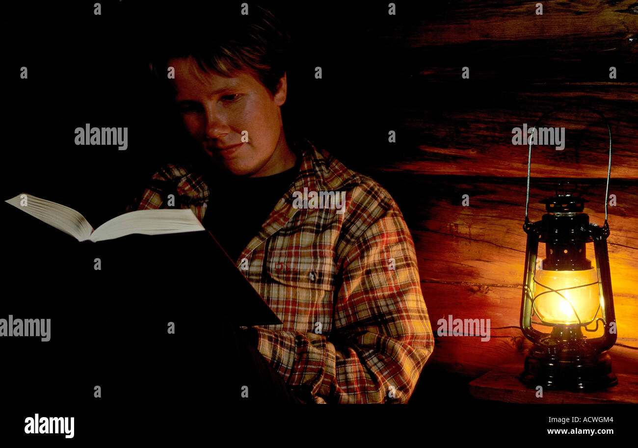 Woman reading book in the light of a kerosene lamp - Stock Image