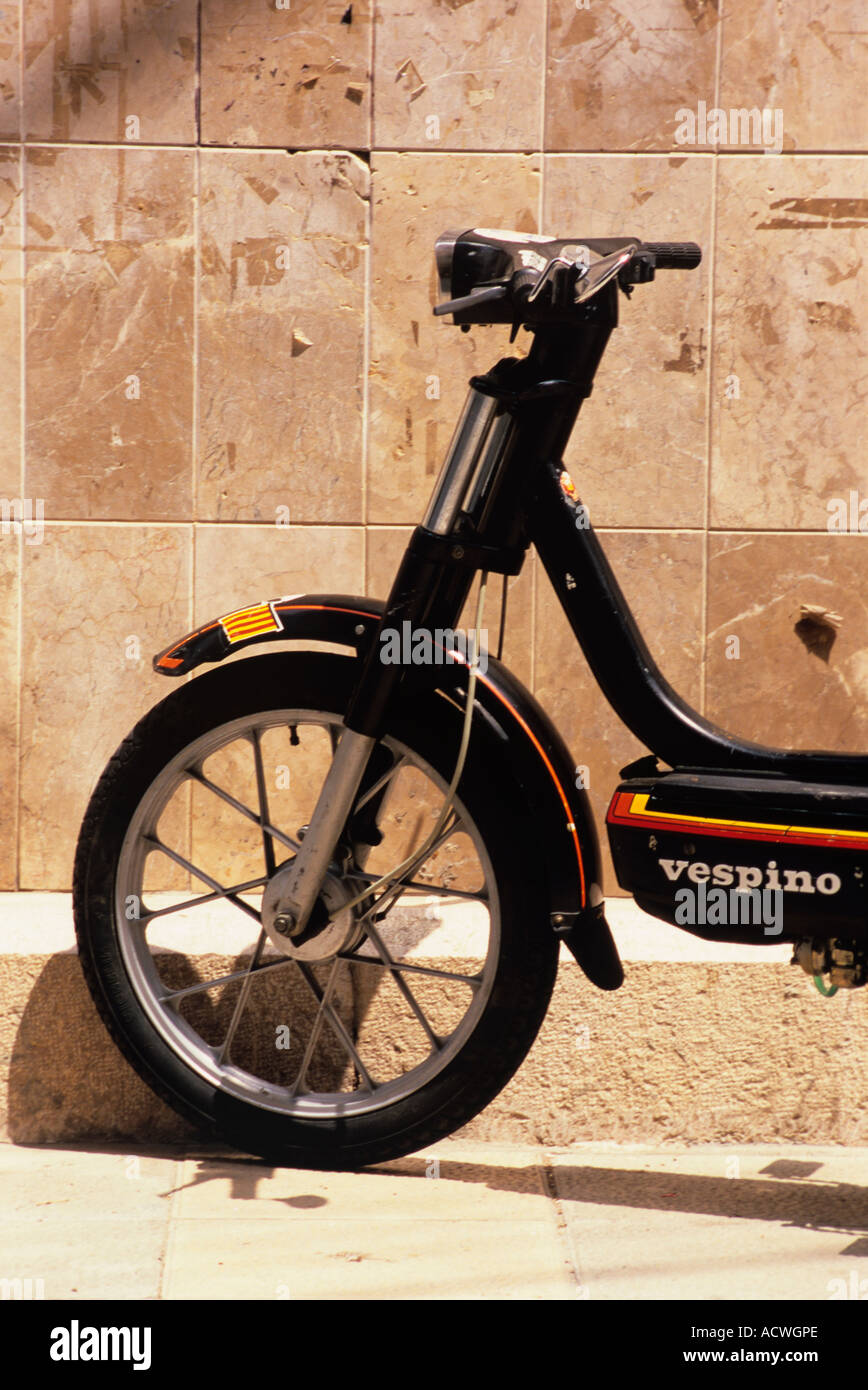 a moped or solex in the mediteranean alongside a wall parked not in use. Stock Photo
