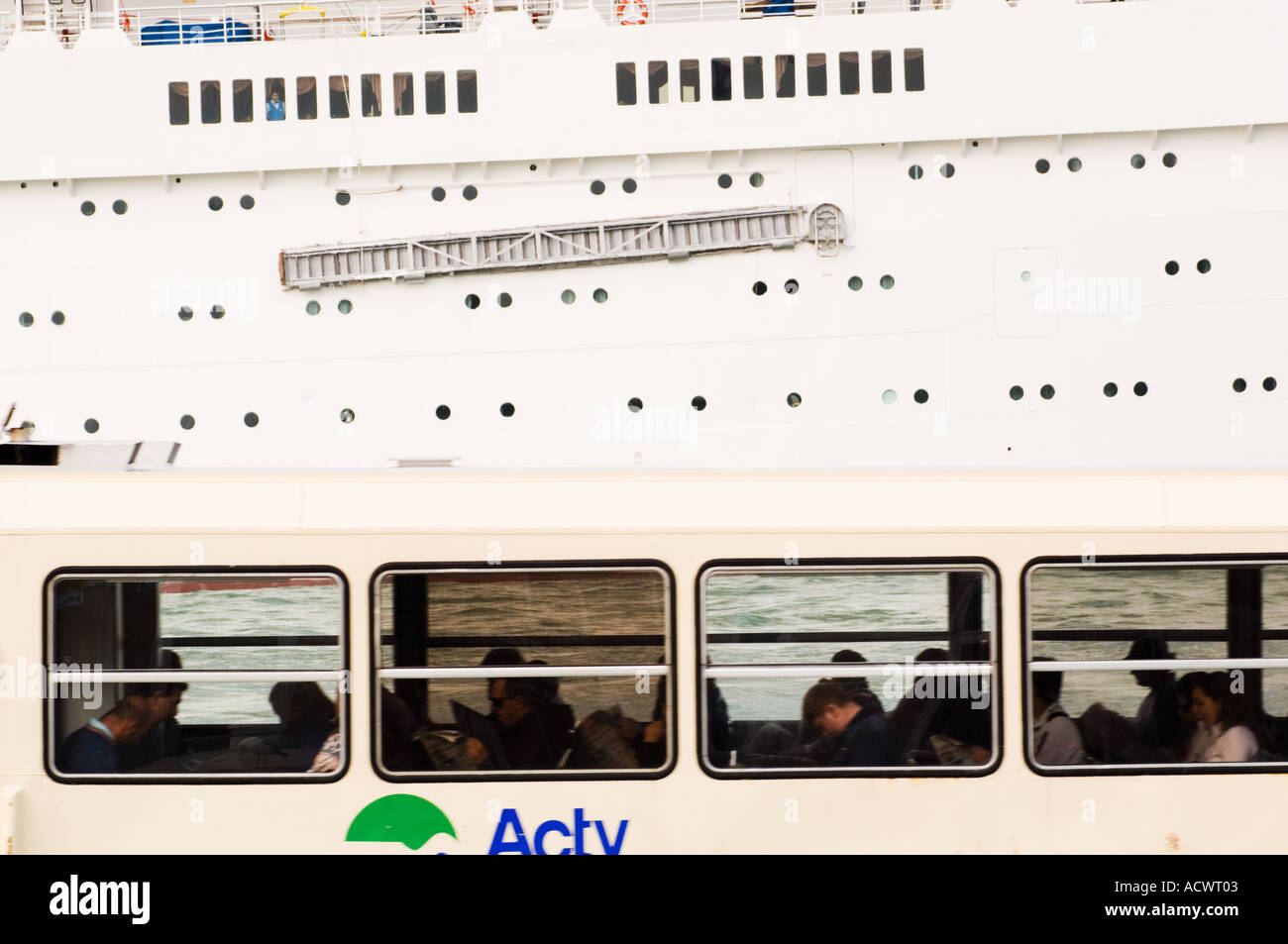 Sides of a small Venice Ferry Bus Boat full of commuters and a large cruise ship passing each other - Stock Image