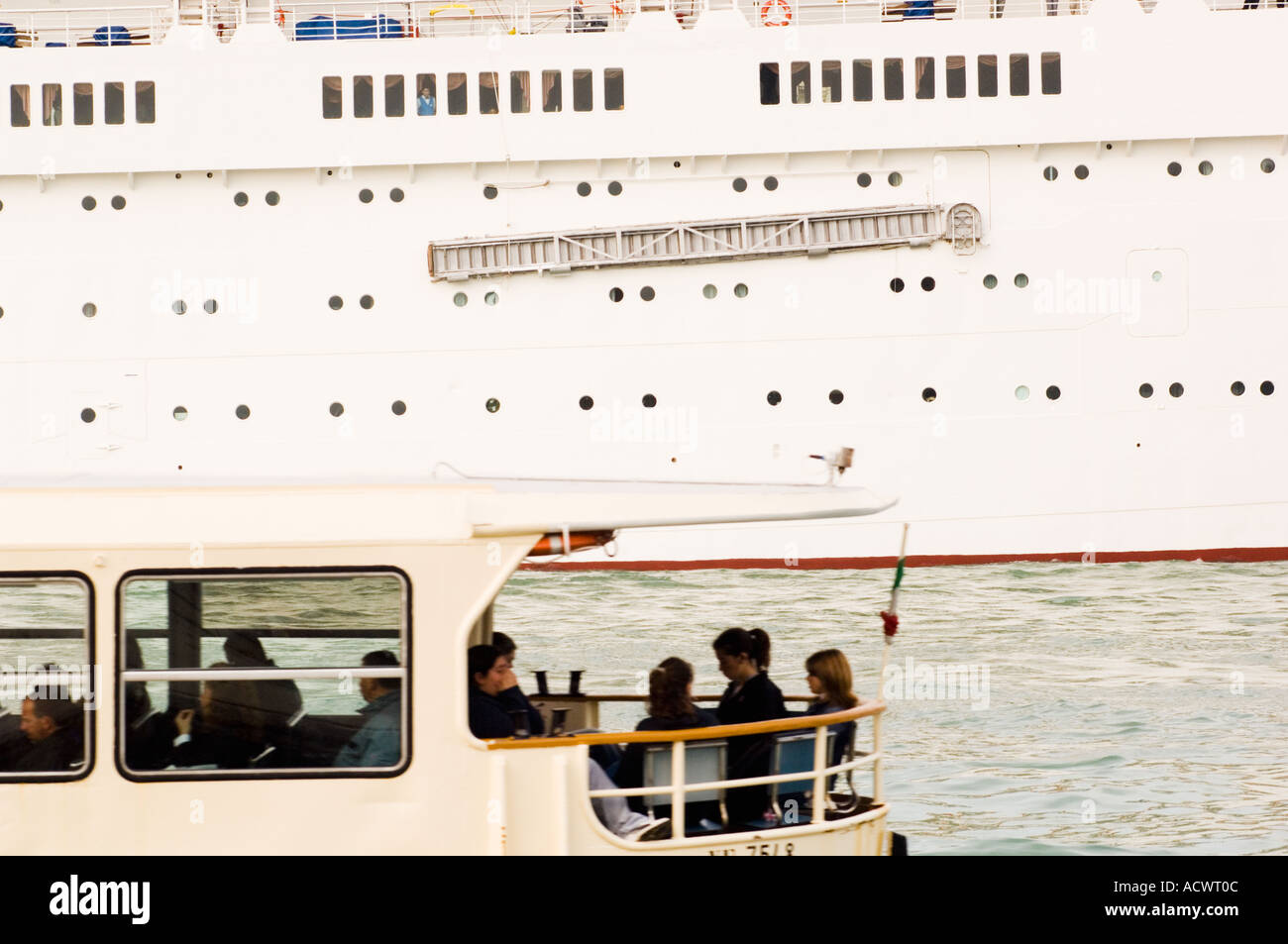 Stern of a small Venice Ferry Bus Boat full of commuters and the side of a large cruise ship passing each other - Stock Image