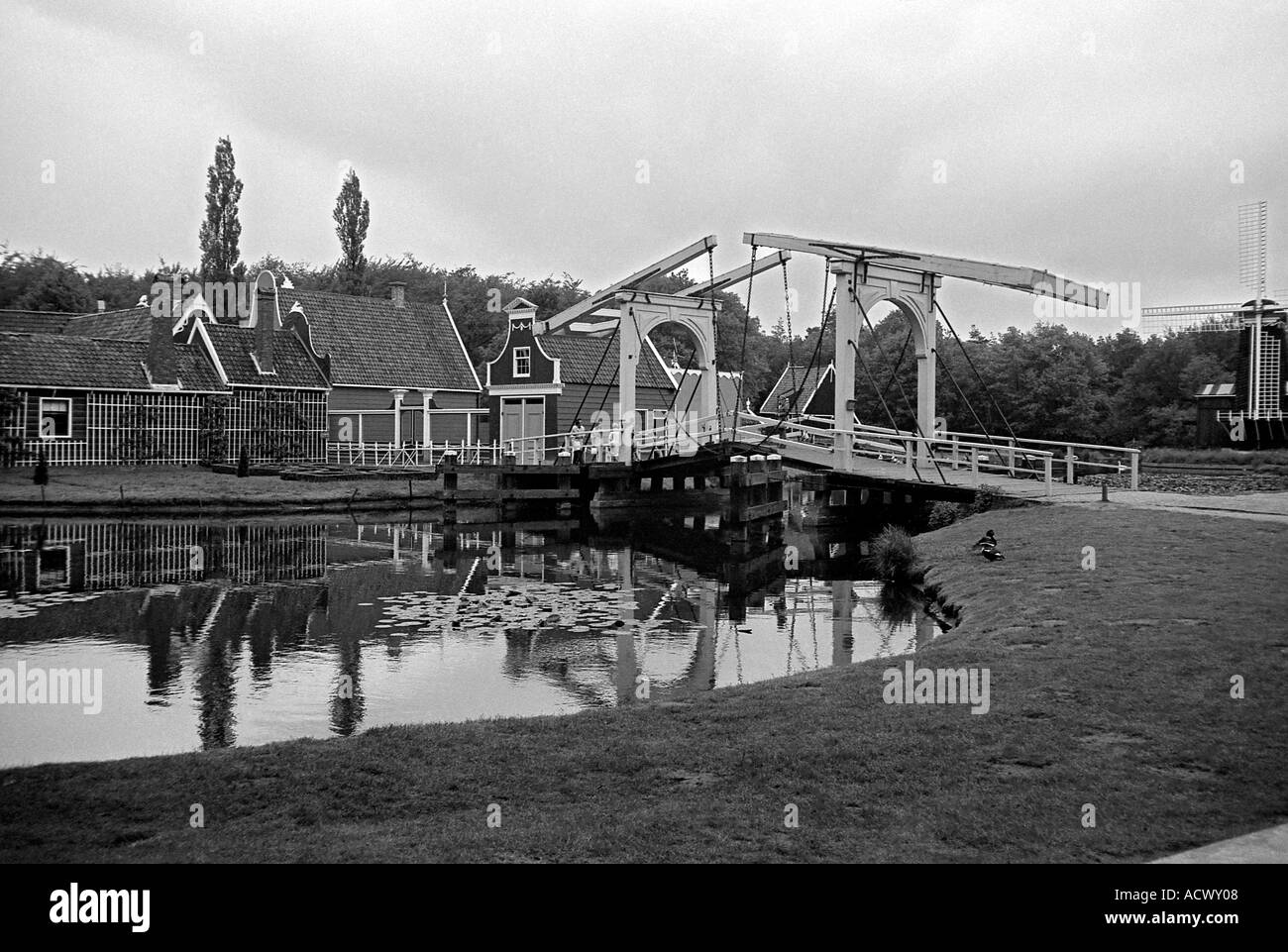Typical classical scene in Holland in an open air museum with counter balanced bridge canal and old wooden houses - Stock Image