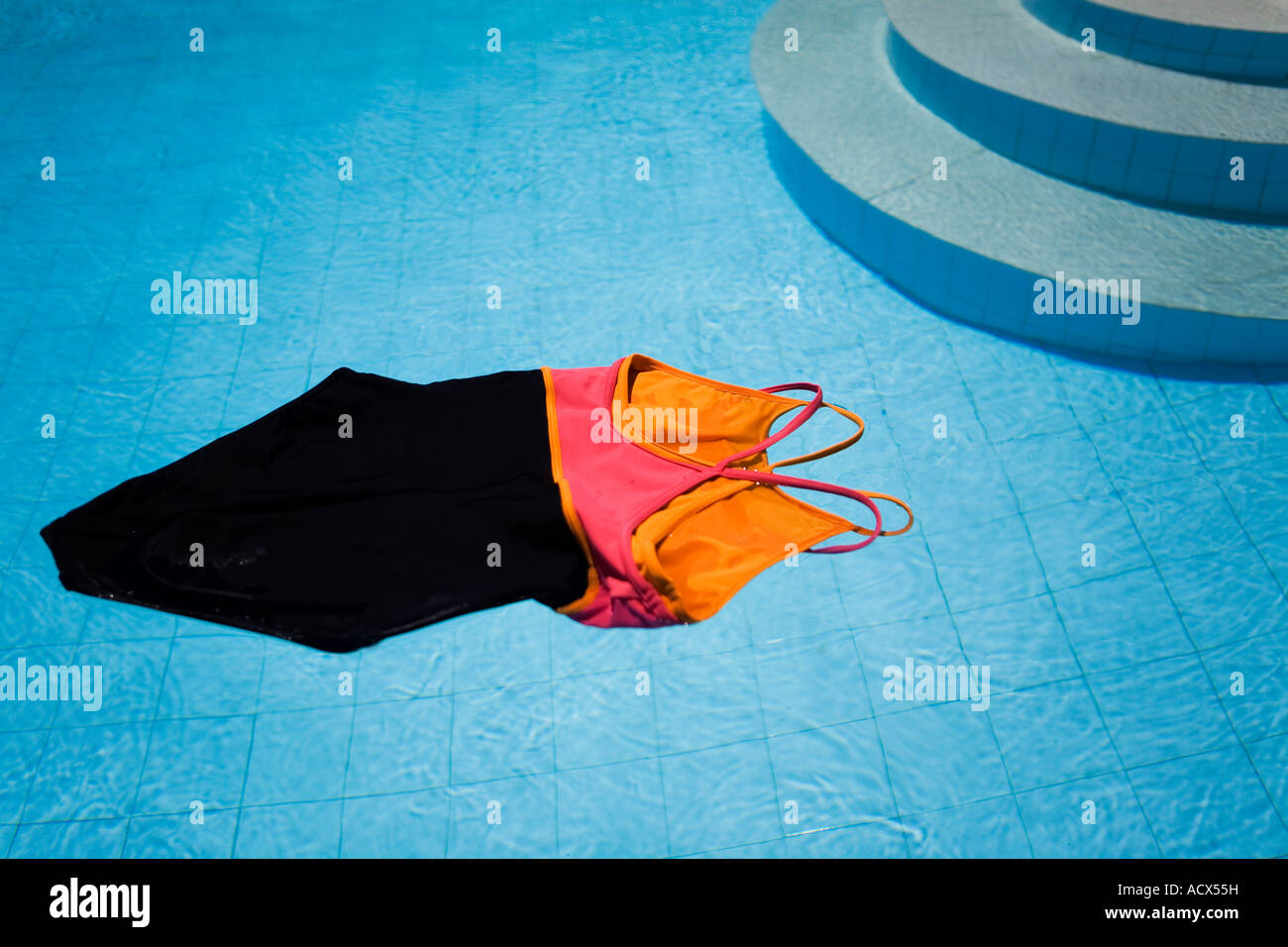 Swimsuit floating in a swimming pool at a villa - Stock Image