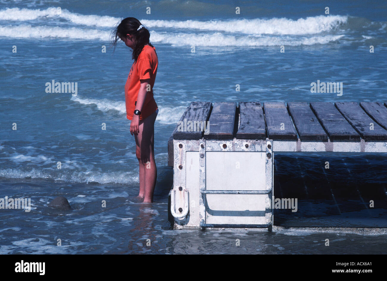 Teenage girl in an orange teeshirt standing beside a pontoon on a beach with white breakers in the background - Stock Image