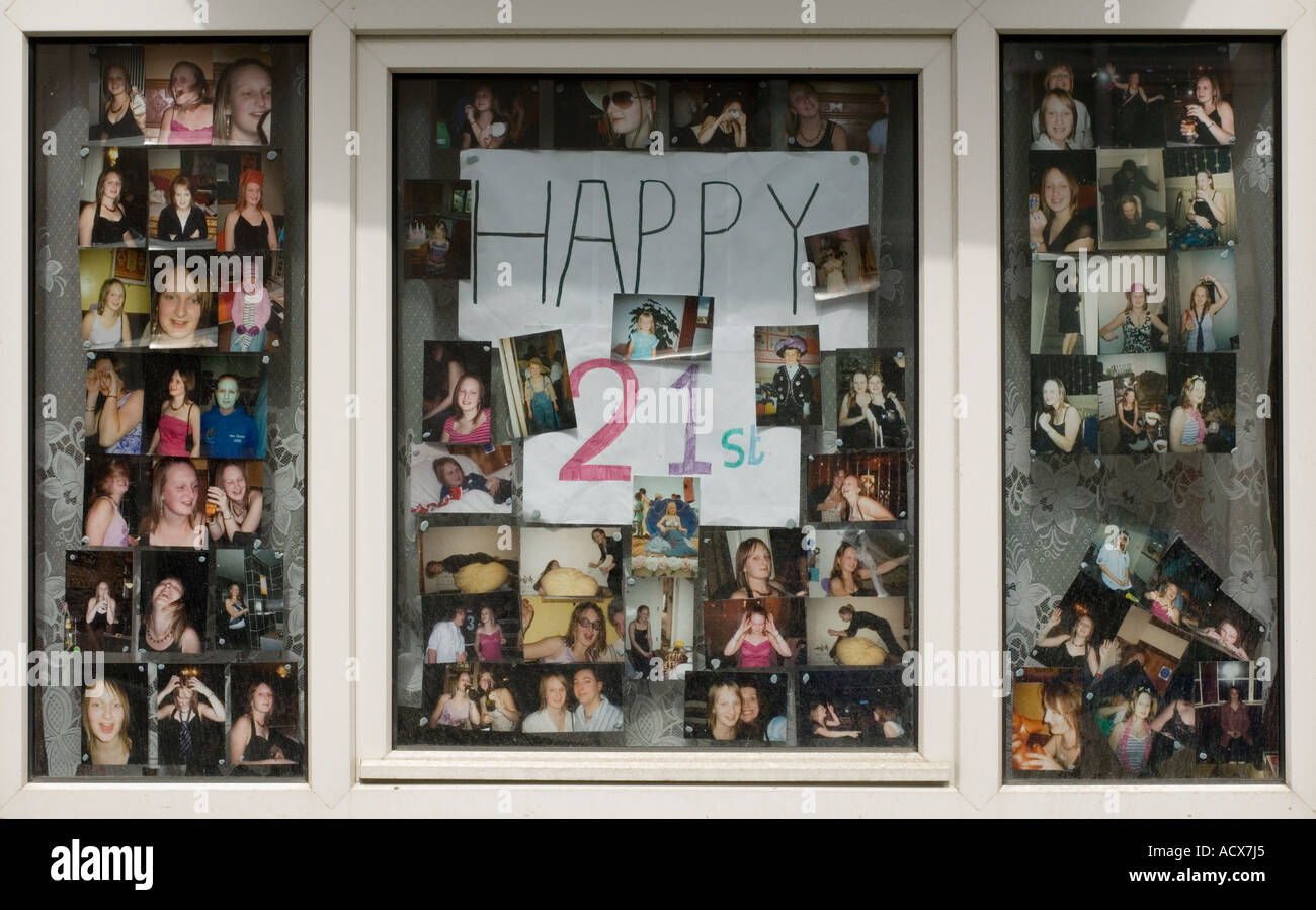 Happy 21st birthday montage of photos in the window of  a bed sit flat - Stock Image