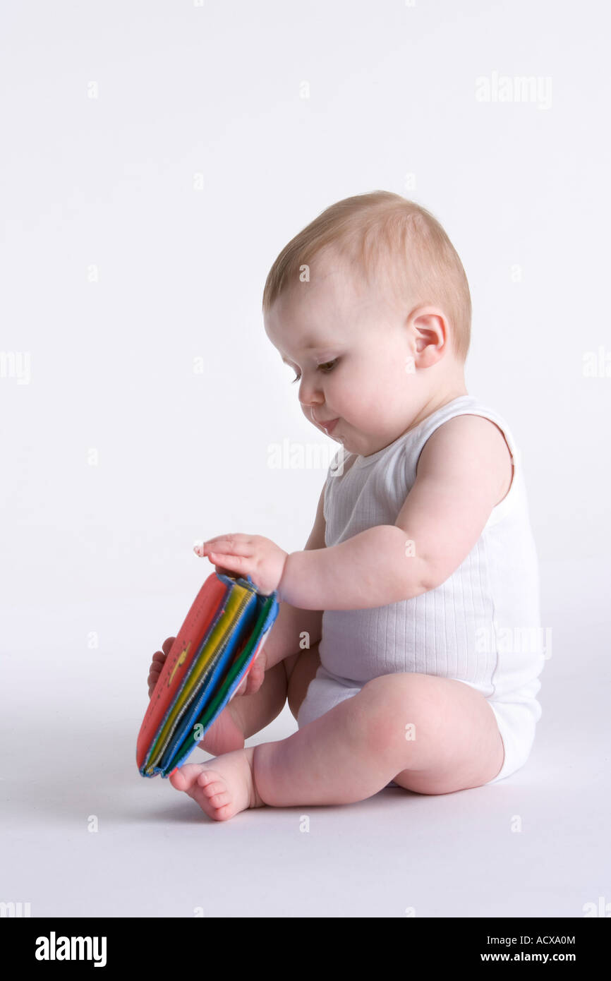 Baby boy with a textile toy book - Stock Image