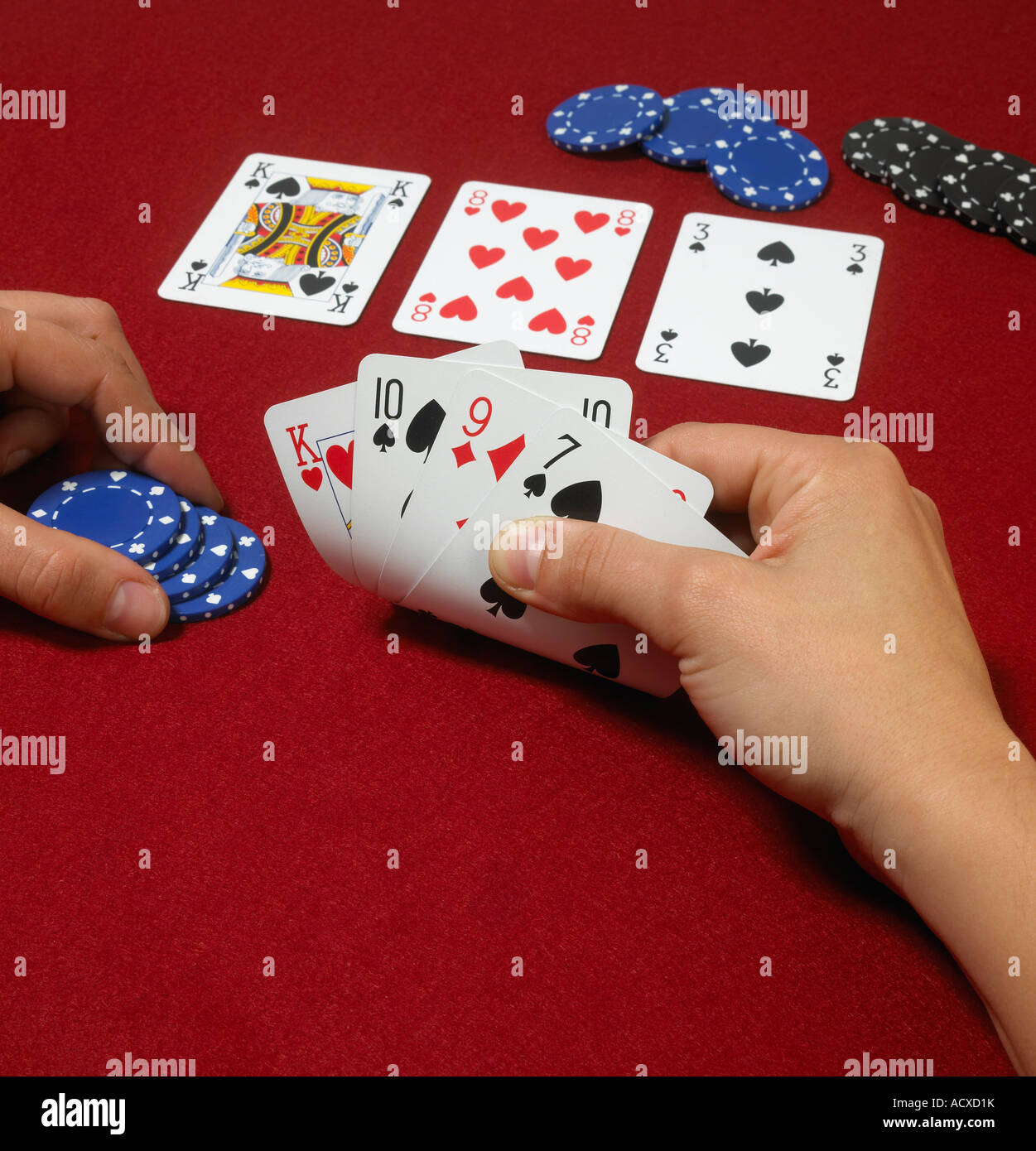 Poker hand with players hands against red baize - Stock Image