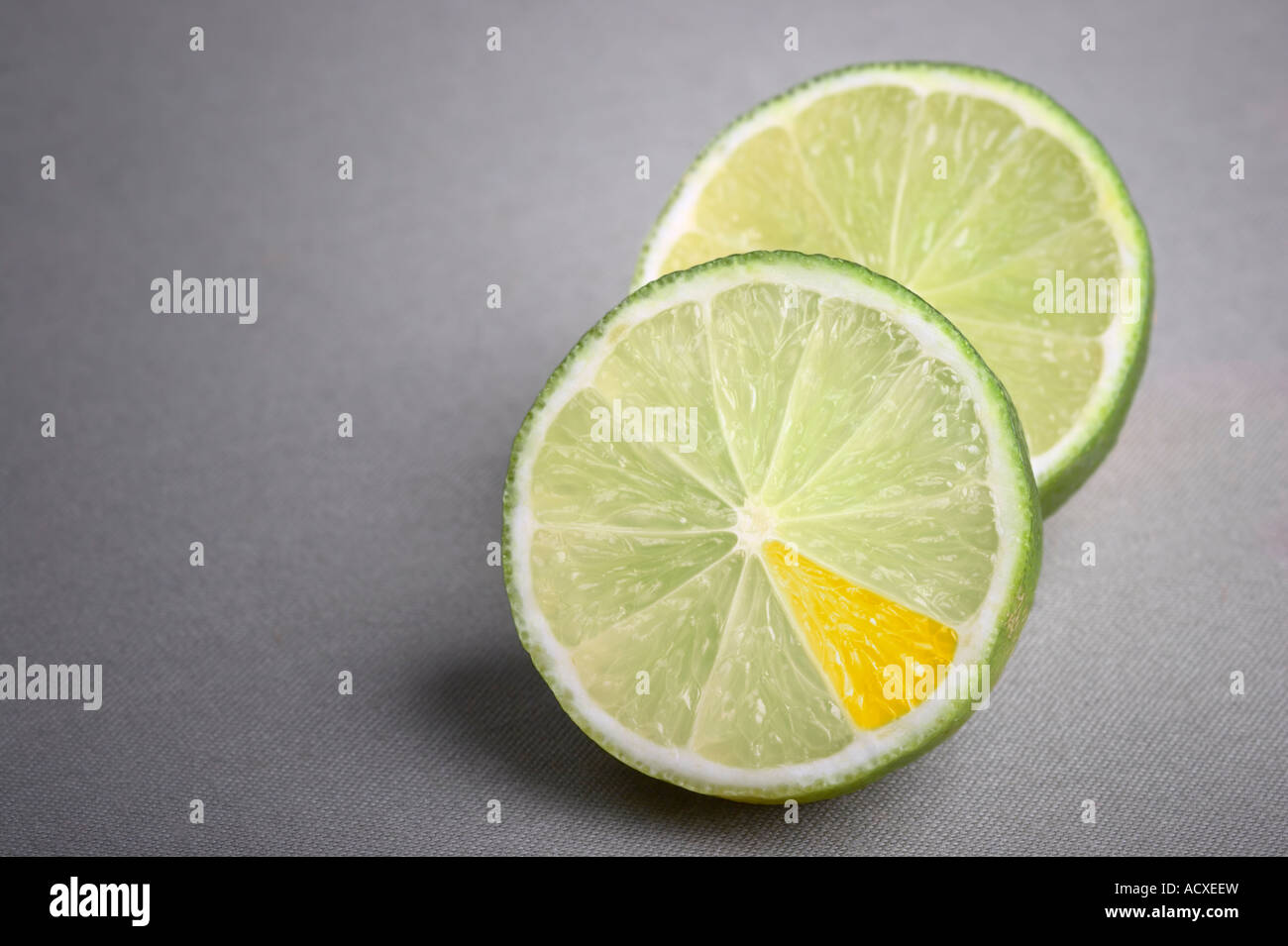 Slices of Lime fruits with one segment colored orange on a gray cloth background - Stock Image