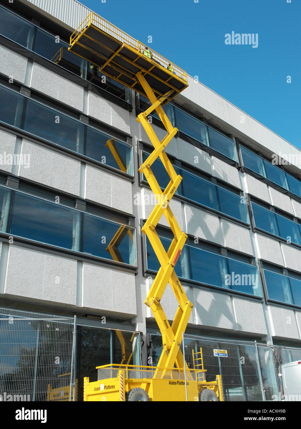 scissor lift working on glass building Stock Photo: 4323738 - Alamy