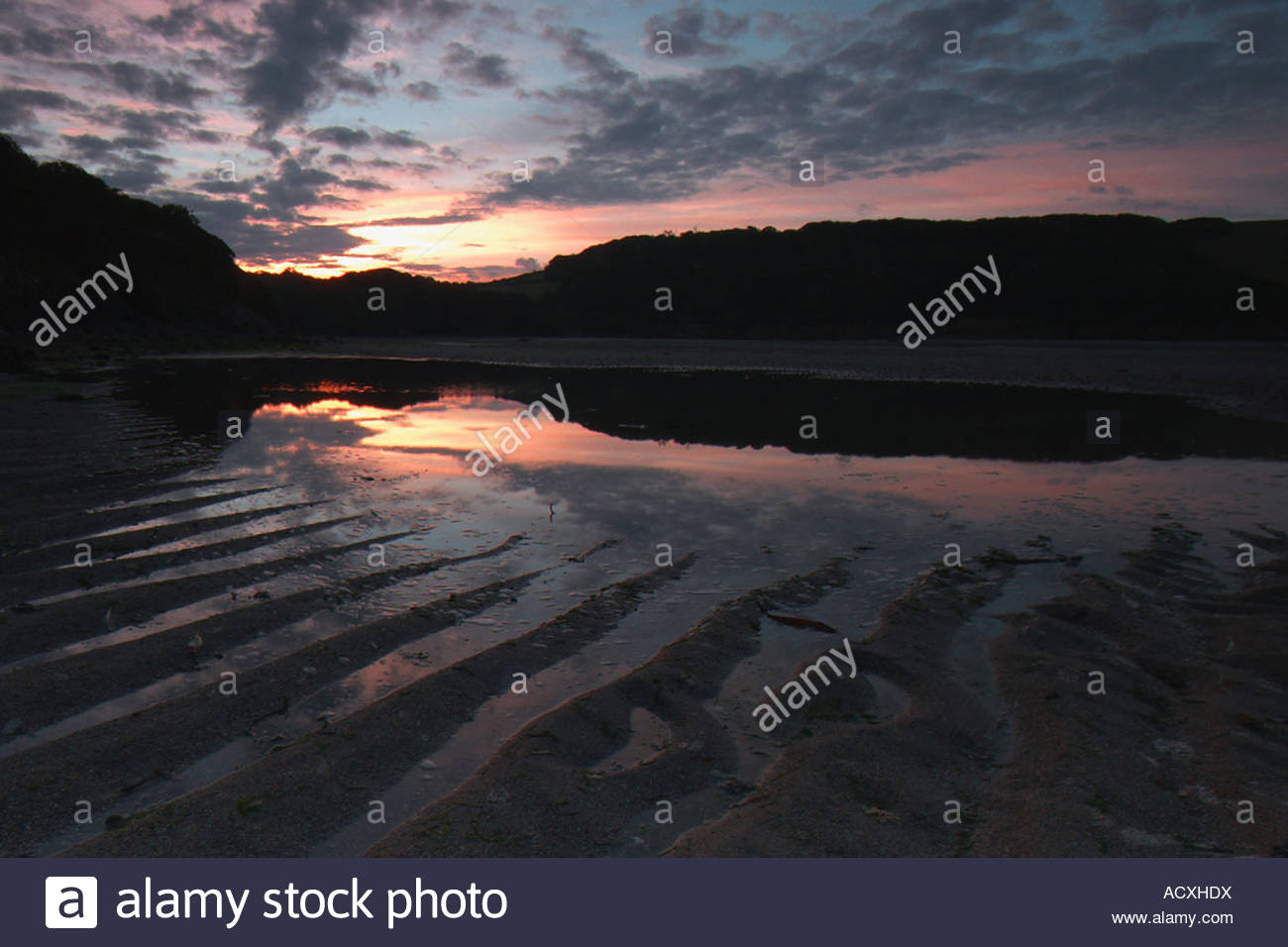 the sunrise reflecting off of the ripples in the sand of the river Erme in South Hams area of Devon - Stock Image