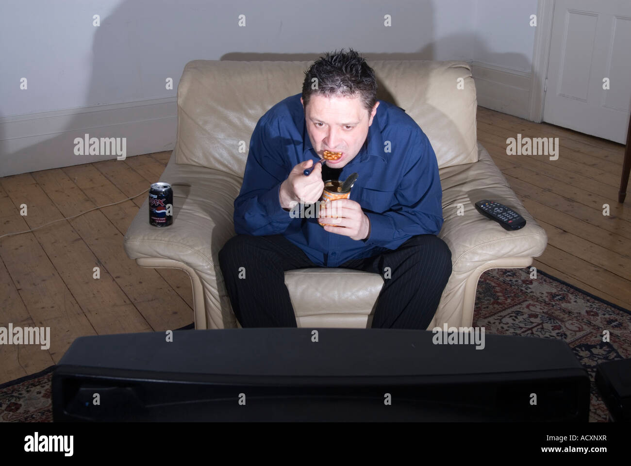 Single man eating dinner in front of television England UK - Stock Image