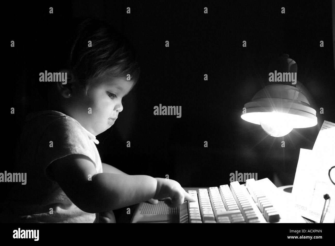 Baby girl typing on a PC keyboard in the evening - Stock Image