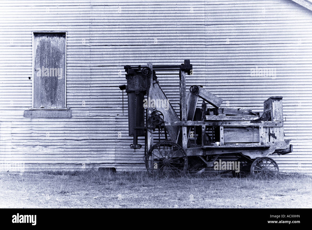 an old wool baler in front of a barn in purple toning - Stock Image