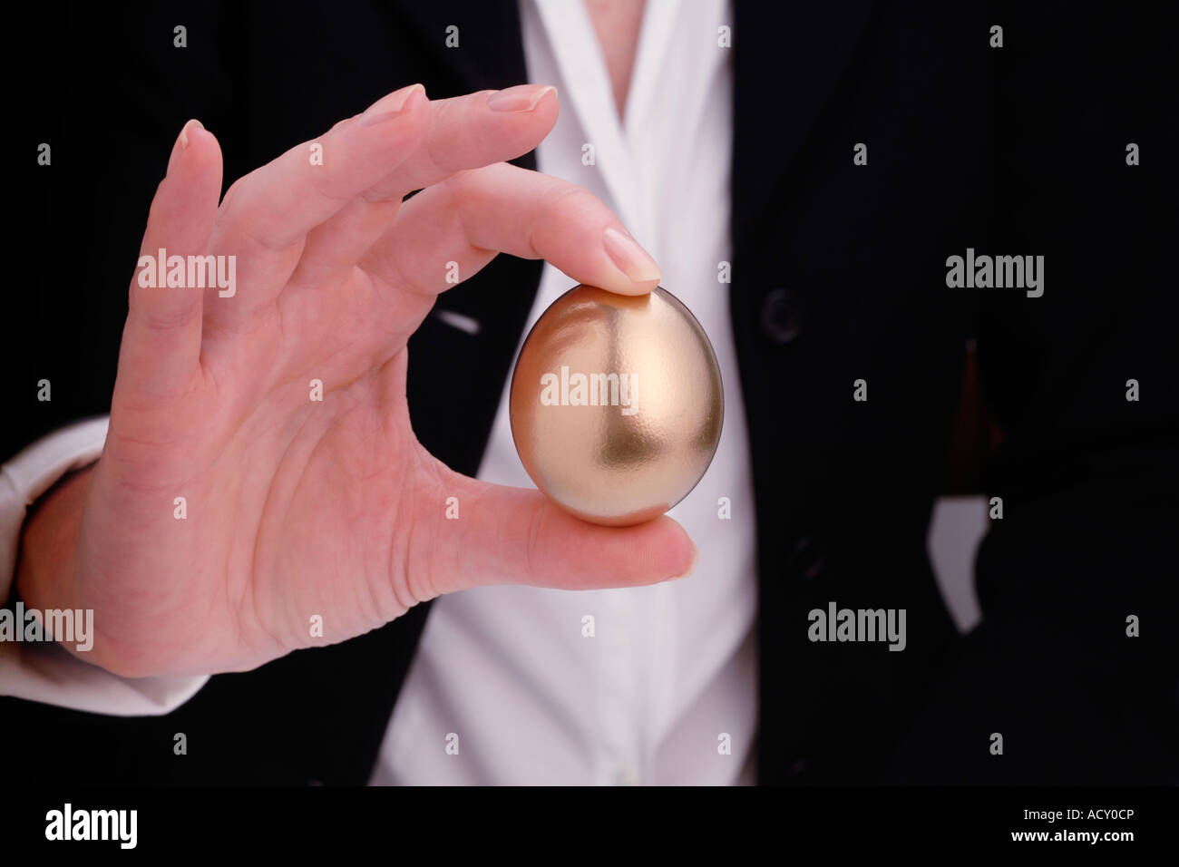 Woman holding golden egg - Stock Image