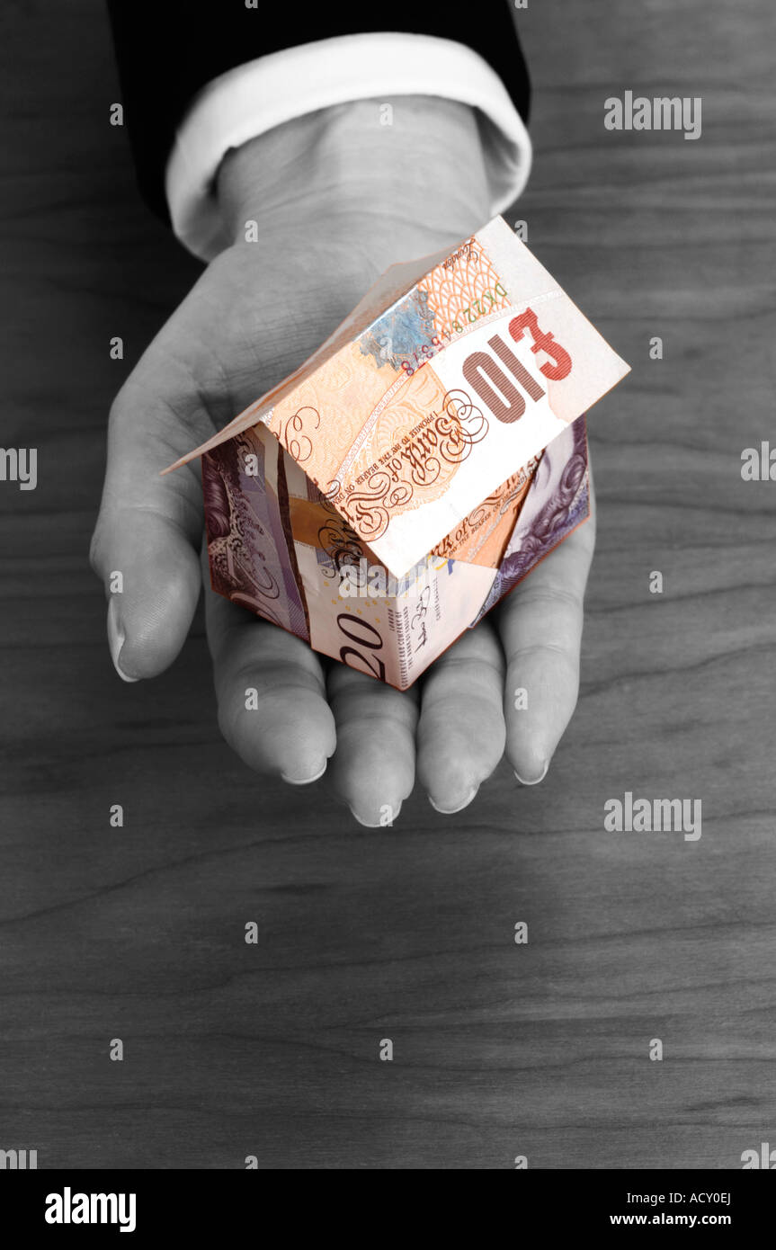 Woman holding house made of 10 and 20 pound notes - Stock Image