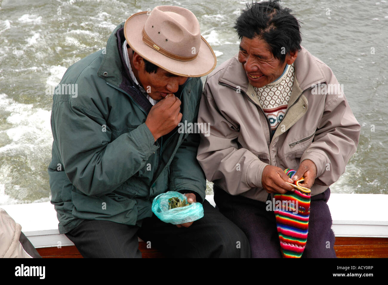 Old couple chatting on a boat while they share their coca leaves Titikaka lake Bolivia - Stock Image