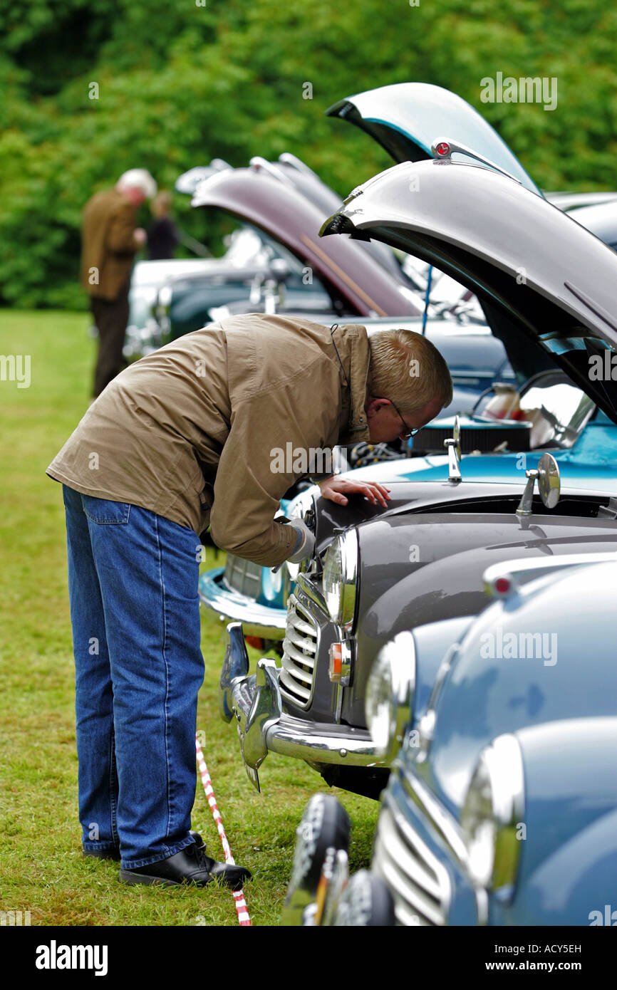 Man looks under bonnet of one of the old Morris Minor cars lined up at vintage car show at Fyvie Castle, Aberdeenshire, - Stock Image