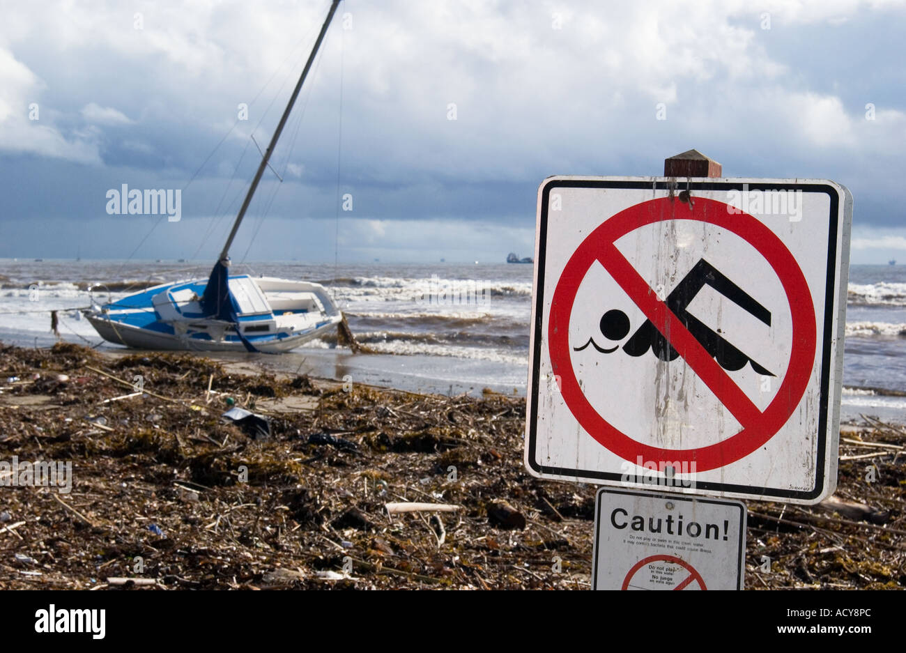 Shipwreck sailboat and no swimming sign due to high levels of water pollution after winter storm, Santa Barbara, Stock Photo