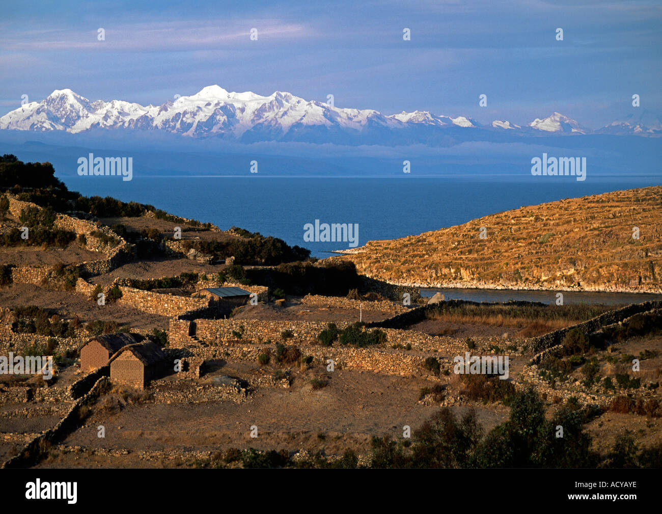 NEVADO ILLAMPU 7010 M is visible behind the Village of CHALLAPAMPA on ISLE DEL SOL LAKE TITICACA - Stock Image