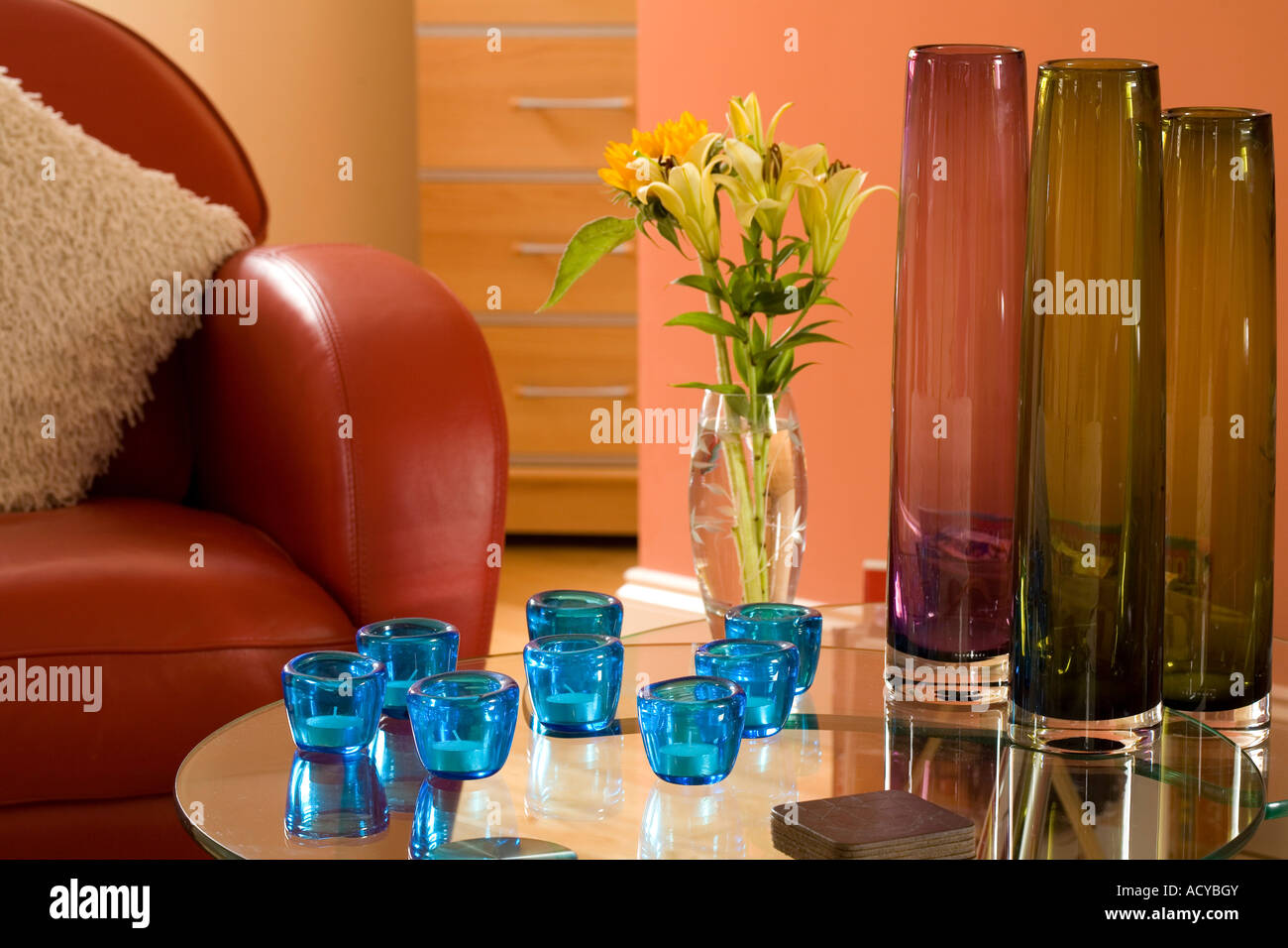 Living area with coloured glass vases and candle holders on glass surface and sofa to left. - Stock Image